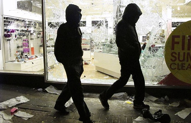 Hooded youths walk past a looted Debenhams store in Clapham Junction during the August 2011 riots.